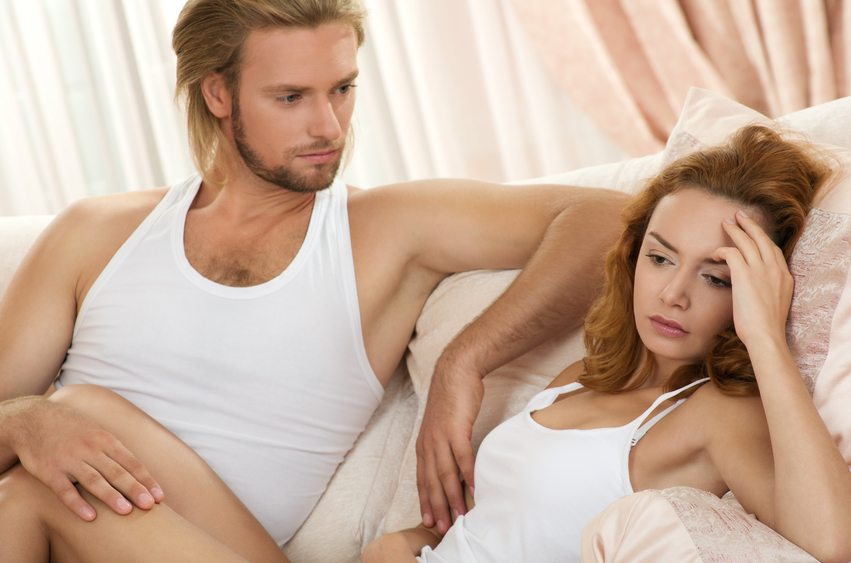 young upset couple lying in a bed having problem